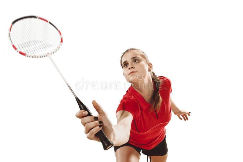 Junge Frau, die Badminton über weißem Hintergrund spielt stockfoto