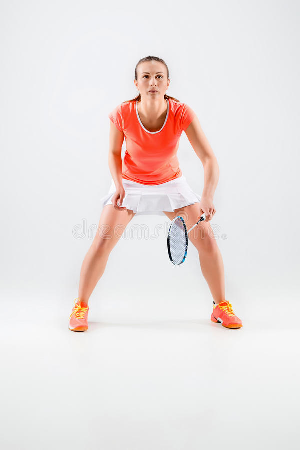 Junge Frau, die Badminton über weißem Hintergrund spielt lizenzfreie stockfotos