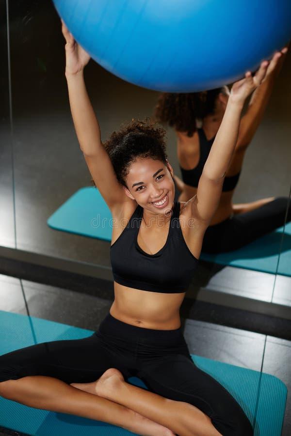 Junge Frau, die Balancenball hält und zur Kamera mit glänzendem Lächeln schaut lizenzfreies stockbild