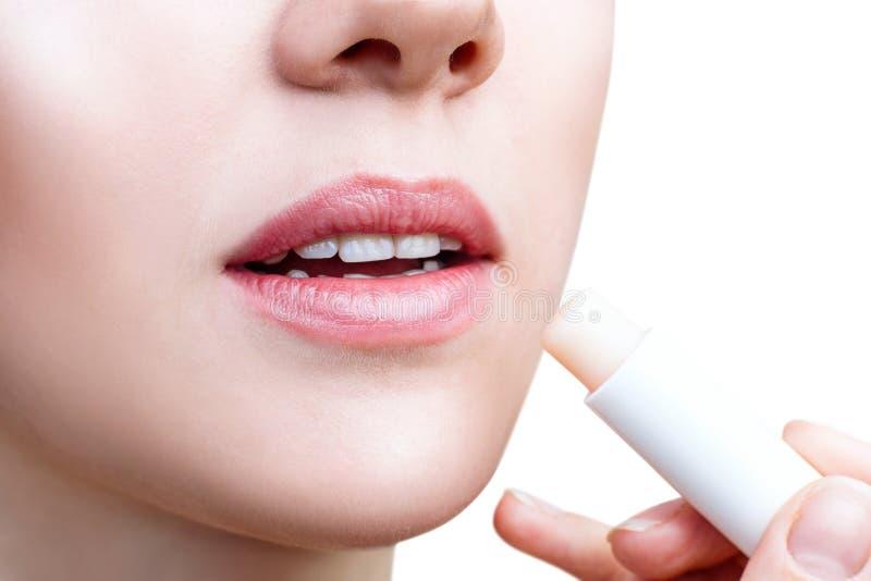 Junge Frau, die Balsam auf Lippen anwendet lizenzfreie stockfotos
