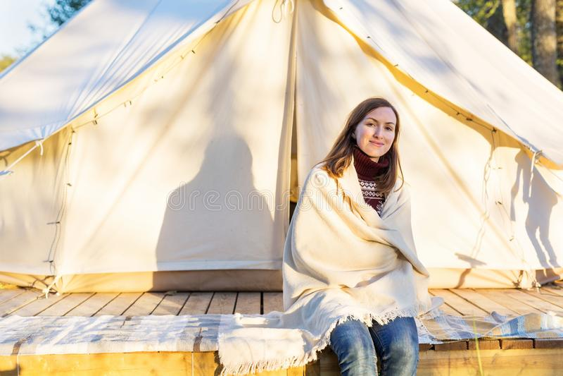 Junge Frau, die bei der Verpackung einer Decke über sitzend nahe Zelt lächelt lizenzfreie stockfotos