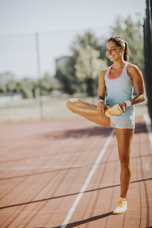 Junge Frau, die Beine vor der Ausbildung ausdehnend trainiert lizenzfreie stockfotos