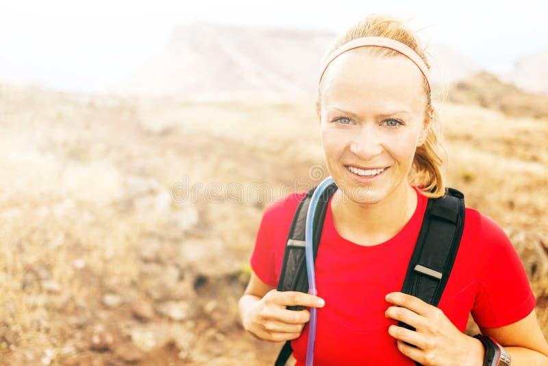 Junge Frau, die in Berge am sonnigen Tag des Winterfalles läuft lizenzfreie stockfotos