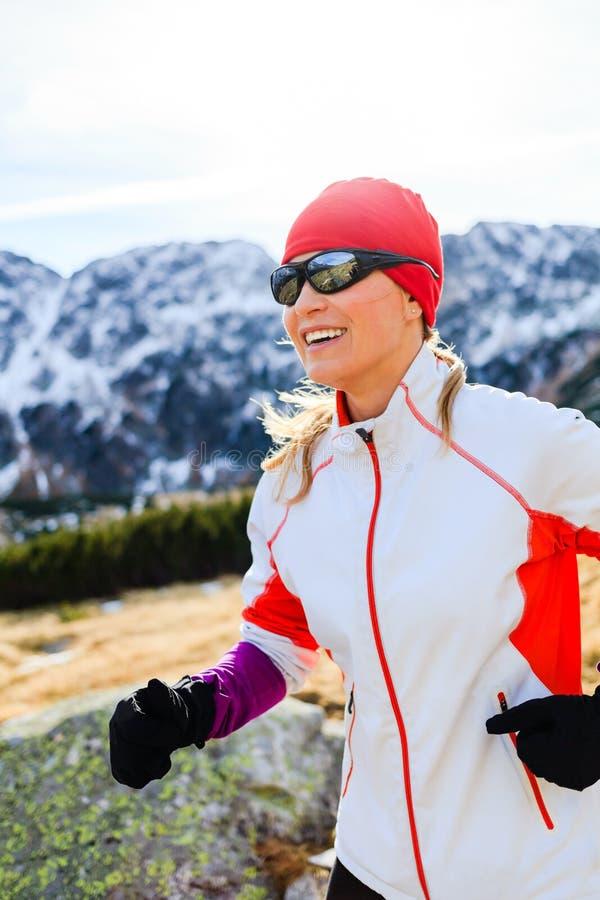 Junge Frau, die in Berge am sonnigen Tag des Winters läuft stockfoto