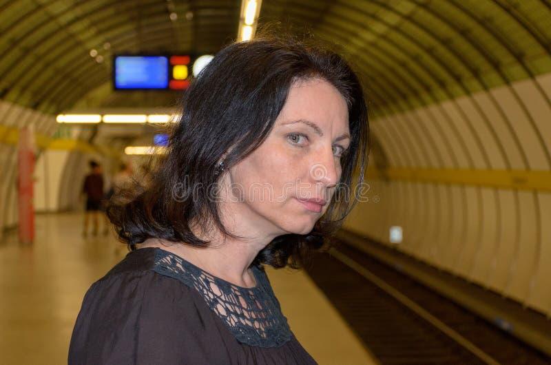 Junge Frau, die besorgt hinunter die Bahnen anstarrt lizenzfreie stockfotografie