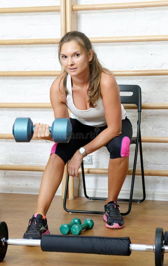 Junge Frau, die Bizepscurlübung mit Dummköpfen in der Turnhalle tut stockbild