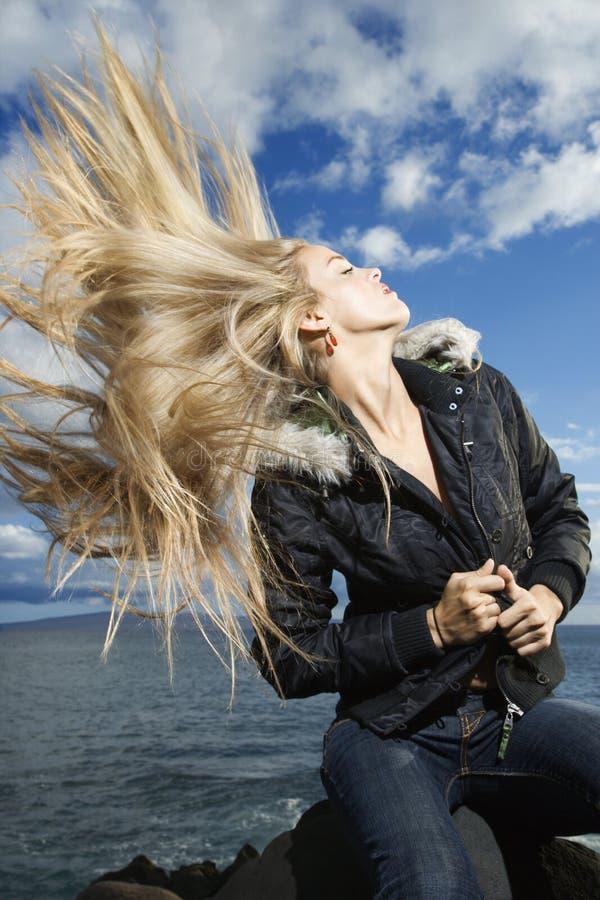 Junge Frau, die blondes Haar wirft stockbild