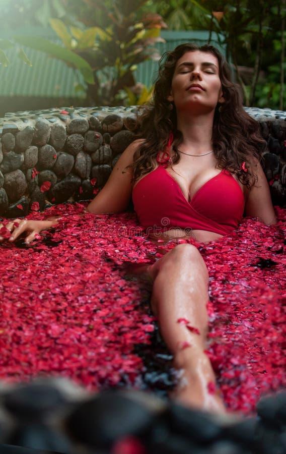 Junge Frau, die Blumenbad im im Freien, organische Hautpflege, Luxusbadekurort im Dschungel sich entspannt Schönheits- und Kaross stockfoto