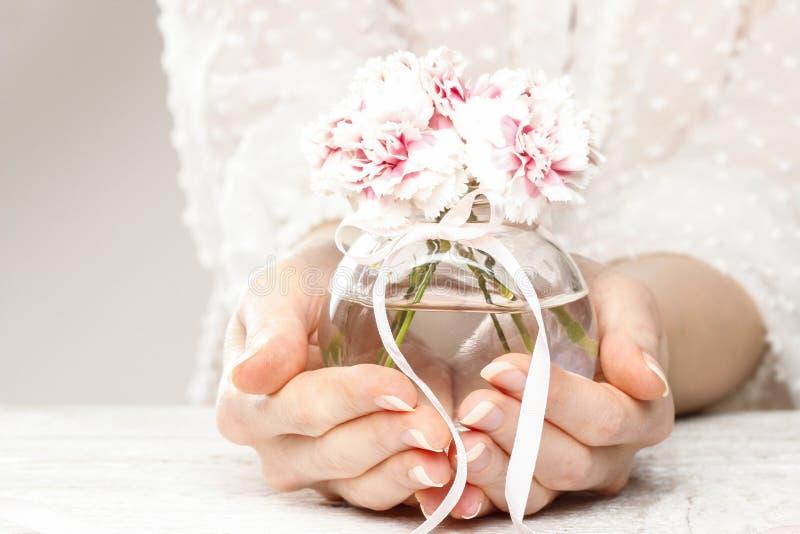 Junge Frau, die Blumenstrauß von Gartennelkenblumen hält lizenzfreie stockbilder