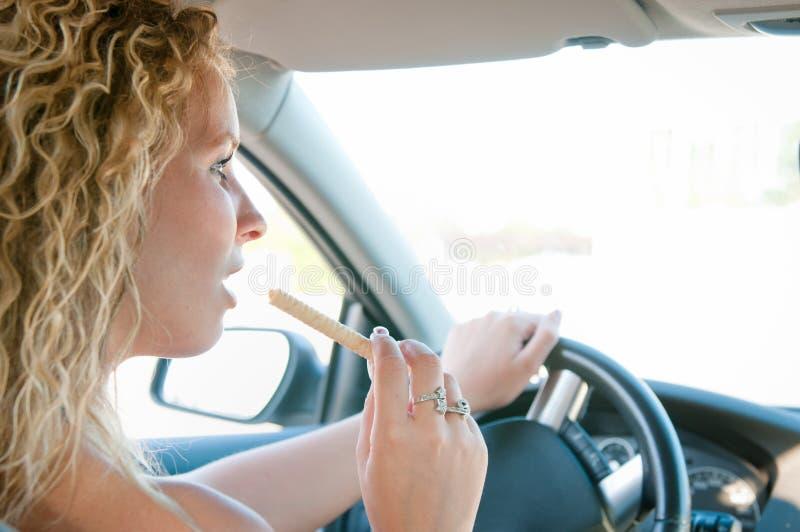 Junge Frau, die Bonbons beim Antreiben des Autos isst lizenzfreie stockbilder