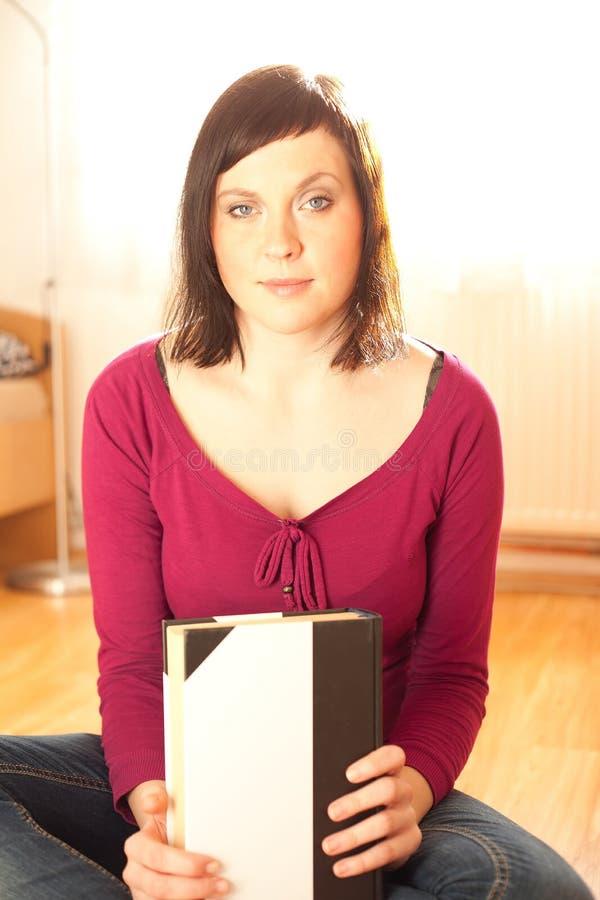 Junge Frau, die Buch hält lizenzfreie stockbilder