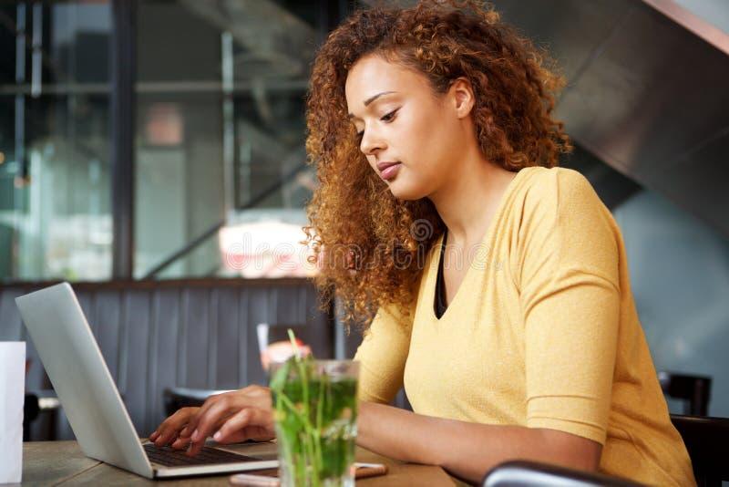 Junge Frau, die am Café mit Laptop sitzt stockfotos
