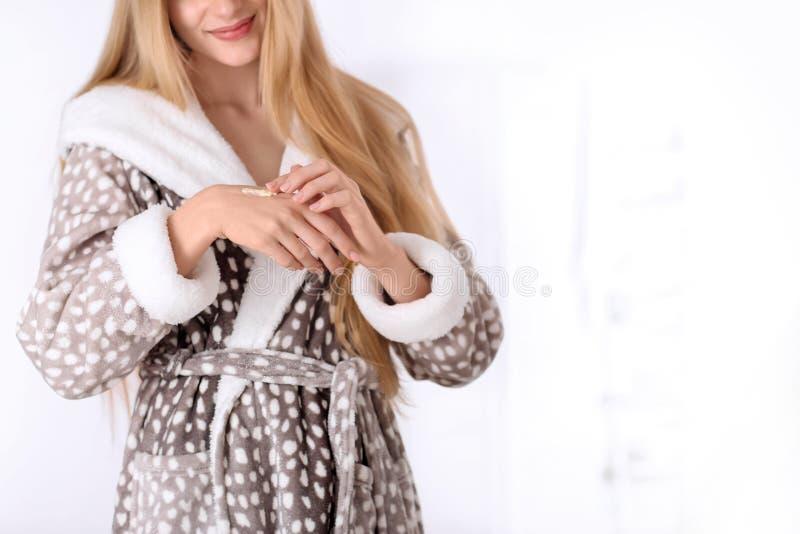Junge Frau, die Creme auf Haut im Badezimmer aufträgt stockbild