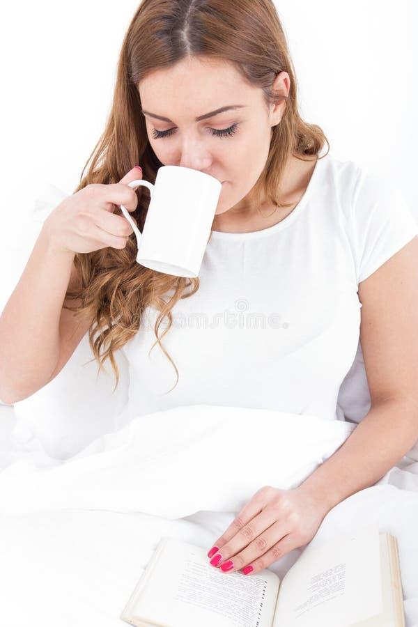 Junge Frau, die das Ablesen und das Trinken des Kaffees im Bett genießt lizenzfreie stockbilder
