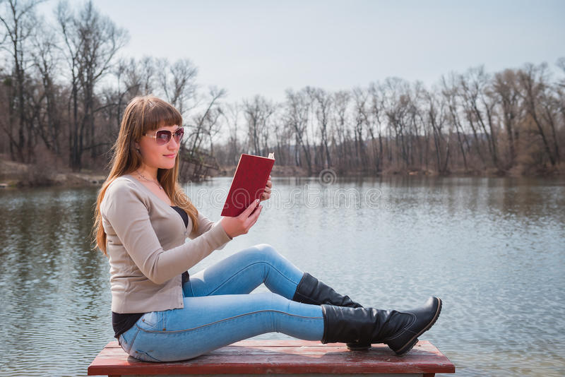 Junge Frau, die das Buch im Freien in der Sonnenbrille, täglichen Lebensstil, Fluss auf dem Hintergrund, Frühling, sonniger Tag l stockfotos