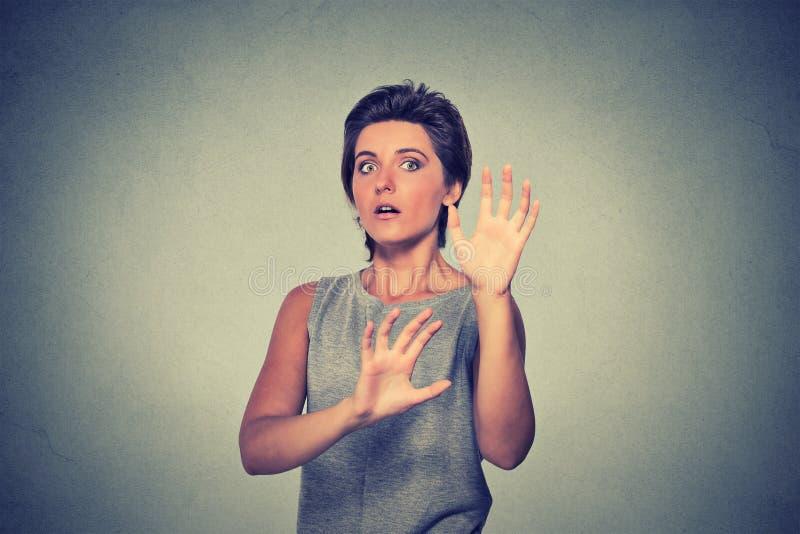 Junge Frau, die das entsetzte erschrockene Versuchen schaut, sich zu schützen lizenzfreies stockfoto