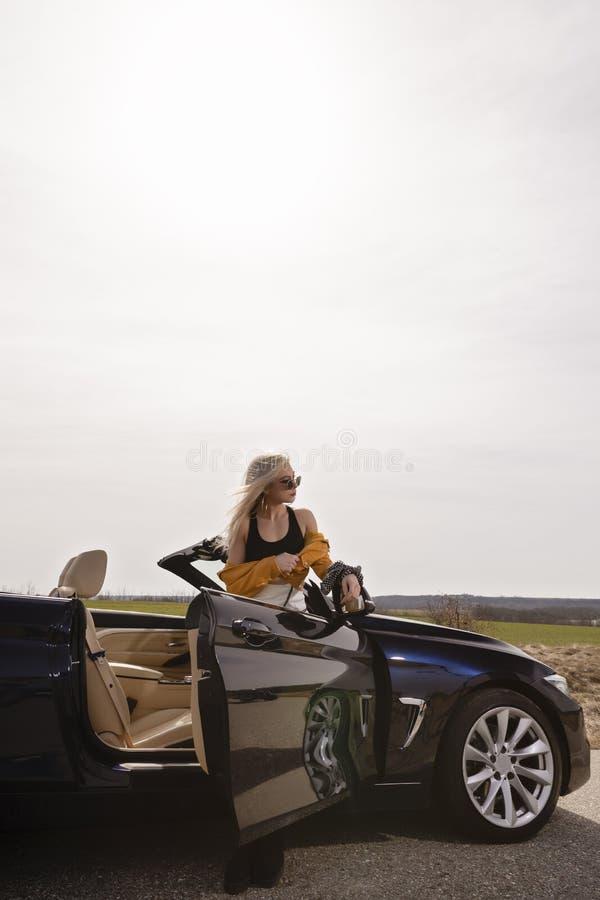 Junge Frau, die das Lehnen auf konvertierbarem Auto aufwirft lizenzfreies stockbild