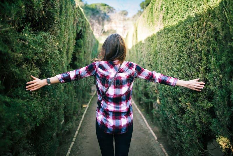 Junge Frau, die in das Parklabyrinth geht lizenzfreie stockfotos