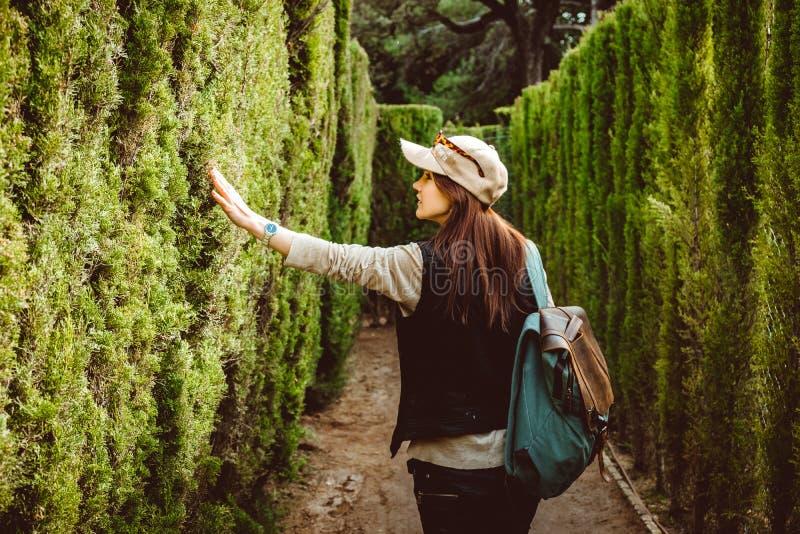 Junge Frau, die in das Parklabyrinth geht stockfoto