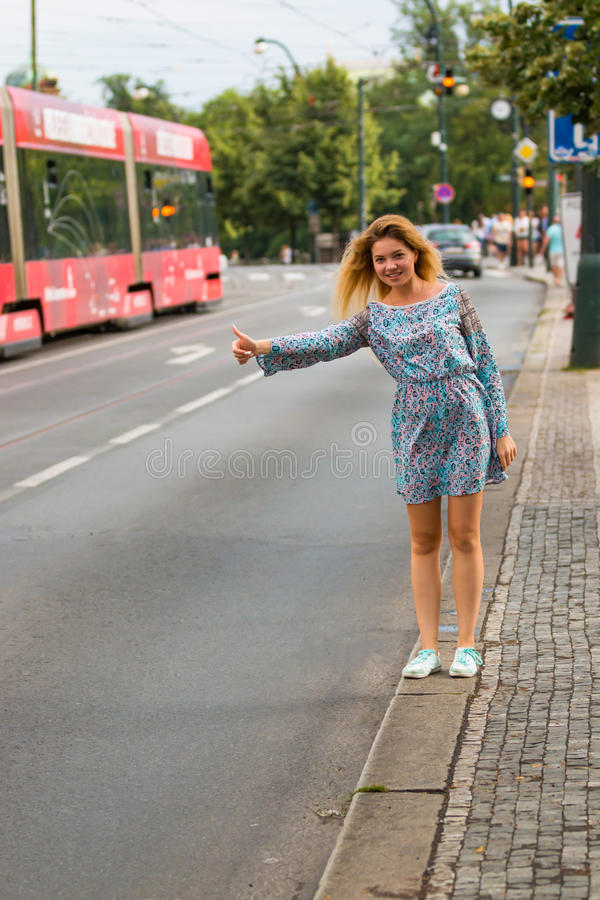 Junge Frau, die das Per Anhalter fahren in einer Straße einer Stadt tut lizenzfreie stockbilder