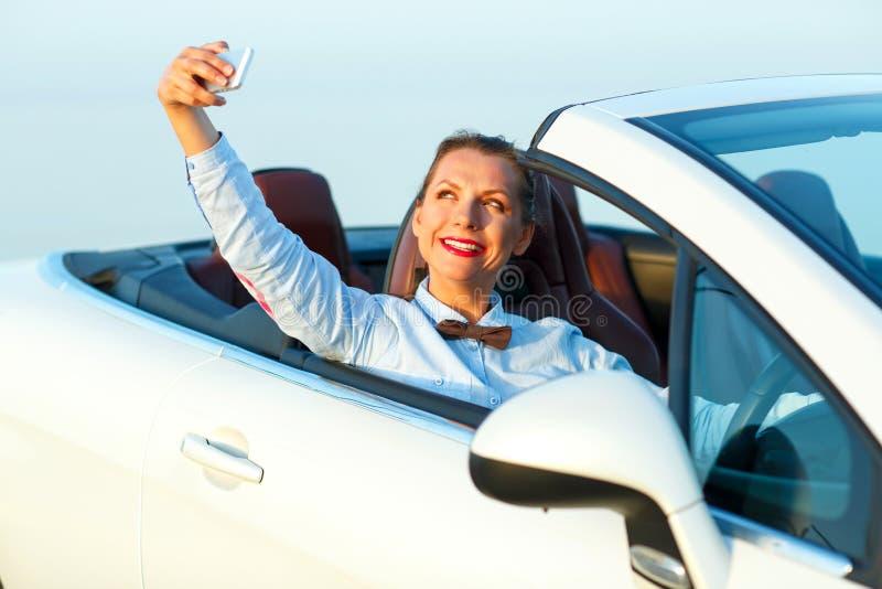 Junge Frau, die das Selbstporträt sitzt im Cabriolet macht stockfotos