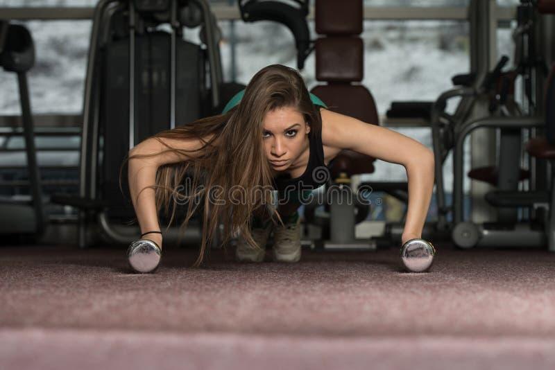 Junge Frau, die das Trainieren drücken, Ups mit Dummköpfen lizenzfreie stockfotos