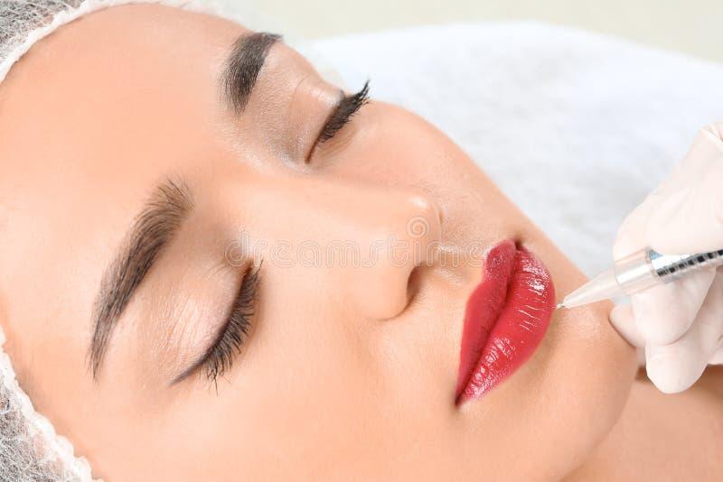 Junge Frau, die dauerhaftes Make-up auf Lippen erhält lizenzfreie stockbilder