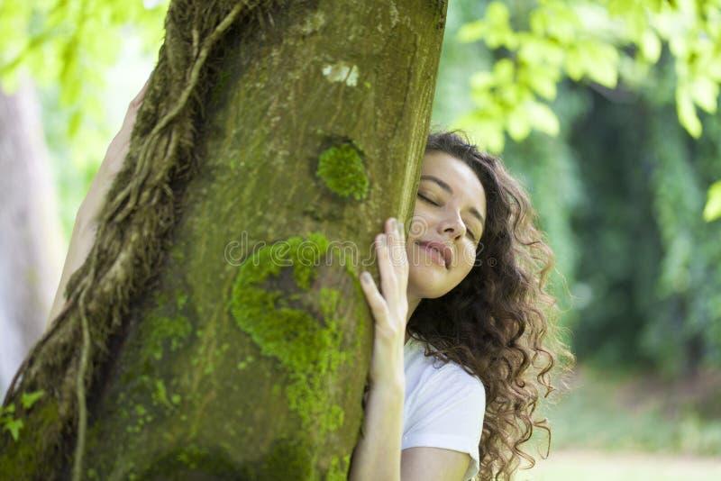 Junge Frau, die den Baum umarmt lizenzfreies stockbild