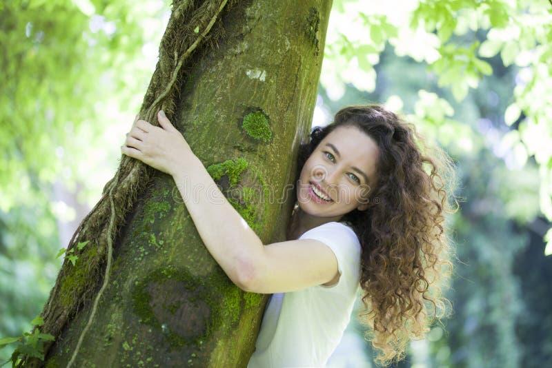 Junge Frau, die den Baum umarmt lizenzfreie stockfotos