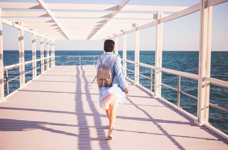Junge Frau, die den blauen Mantel geht nahe dem Meer trägt Rückseitige Ansicht lizenzfreie stockfotos