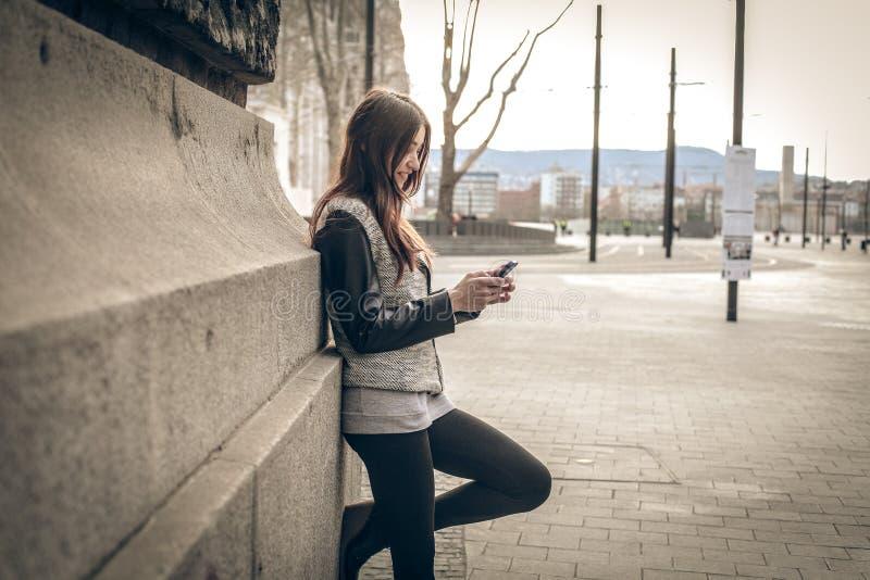 Junge Frau, die den Handy betrachtet lizenzfreie stockbilder