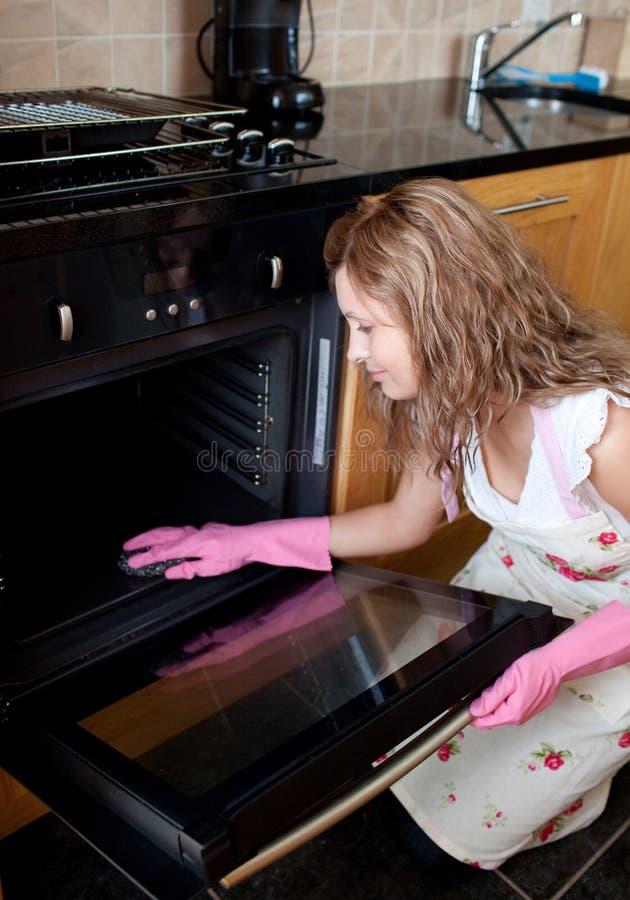 Junge Frau, die den Ofen säubert stockfoto