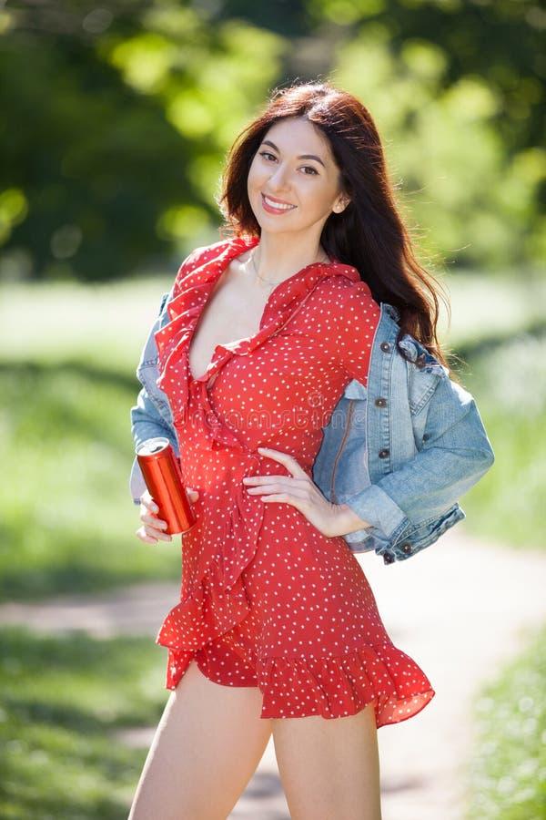Junge Frau, die in den Park geht Schönheitsnaturszene mit buntem Hintergrund Modefrau mit Flasche des Getränks am Sommer sich ent stockfotos
