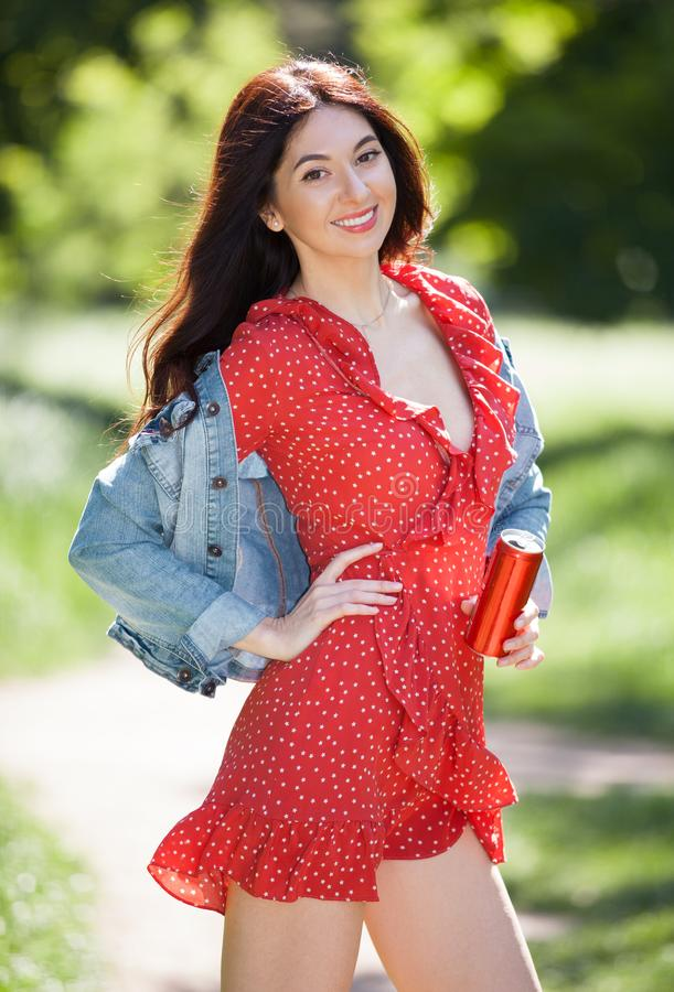 Junge Frau, die in den Park geht Sch?nheitsnaturszene mit buntem Hintergrund Modefrau mit Flasche des Getr?nks am Sommer sich ent lizenzfreie stockfotos