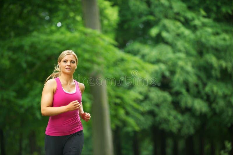 Junge Frau, die in den Park an ihrer Freizeit läuft stockbilder