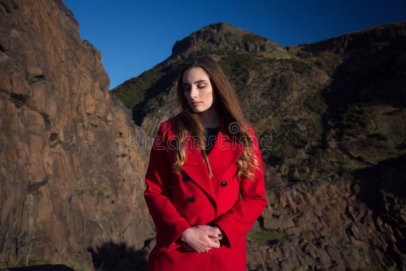 Junge Frau, die den roten Mantel unten schauend und unglücklich trägt stockbilder