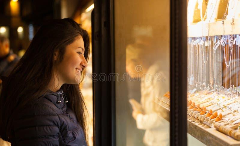 Junge Frau, die den Schaukasten eines Schmucks im Freien betrachtet stockfotos