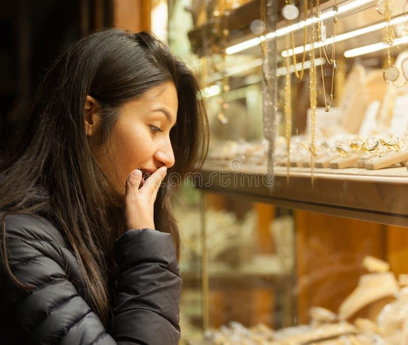 Junge Frau, die den Schaukasten eines Schmucks im Freien betrachtet lizenzfreie stockfotos