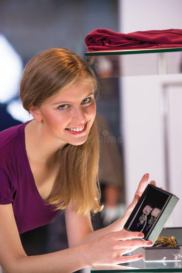 Junge Frau, die den Shopschaukasten betrachtet und Ohrringe nimmt lizenzfreie stockbilder
