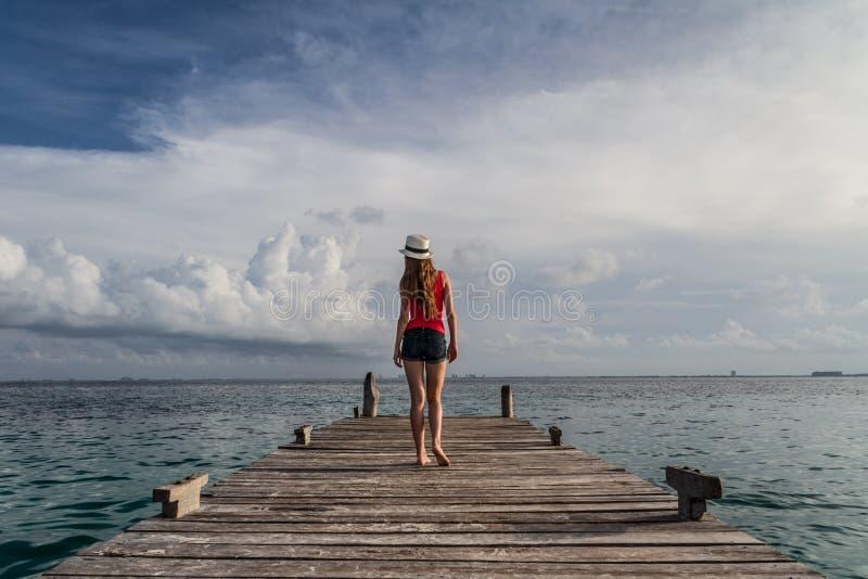 Junge Frau, die den Sonnenuntergang in dem Meer geht und genießt lizenzfreie stockfotografie