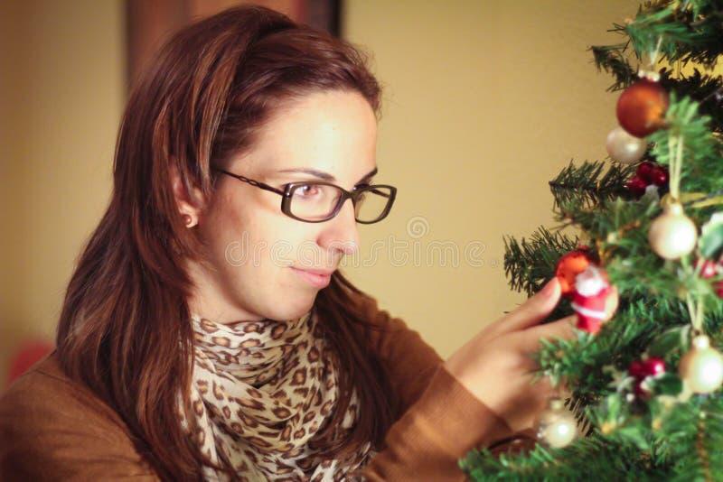 Junge Frau, die den Weihnachtsbaum verziert stockfotos