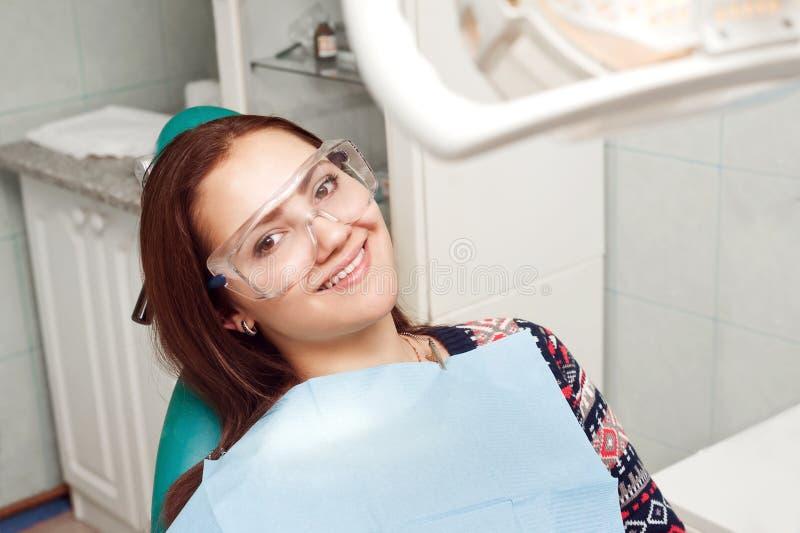 Junge Frau, die den Zahnarzt und das Lächeln besucht lizenzfreies stockfoto