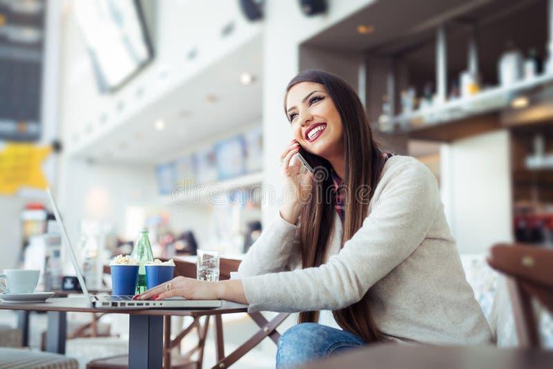 Junge Frau, die in der Cafeteria mit Laptop sitzt und Handy verwendet lizenzfreie stockfotos