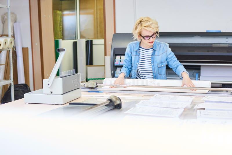 Junge Frau, die in der Druckerei arbeitet lizenzfreie stockfotografie