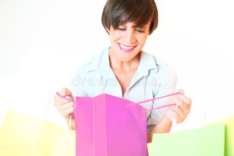 Junge Frau, die in der Einkaufstasche schaut lizenzfreie stockfotografie