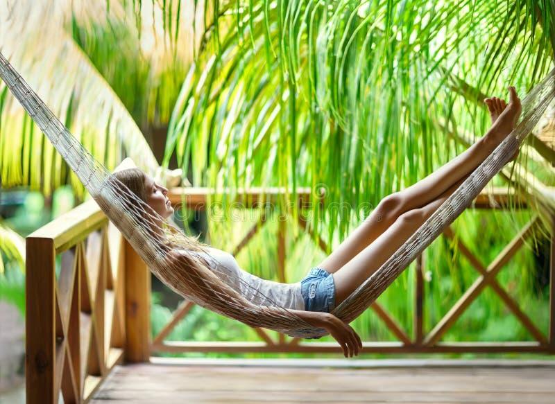Junge Frau, die in der Hängematte in einem tropischen Erholungsort sich entspannt lizenzfreie stockfotos