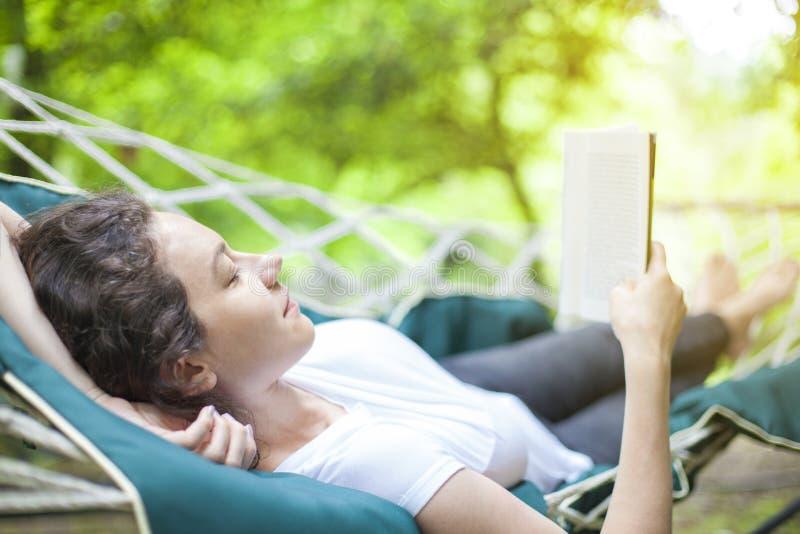 Junge Frau, die in der Hängematte mit Buch sich entspannt lizenzfreie stockfotos