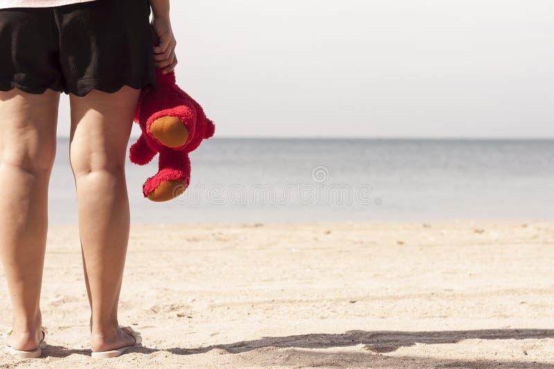Junge Frau, die in der Hand auf dem Strand mit einem roten Teddybären steht lizenzfreie stockbilder