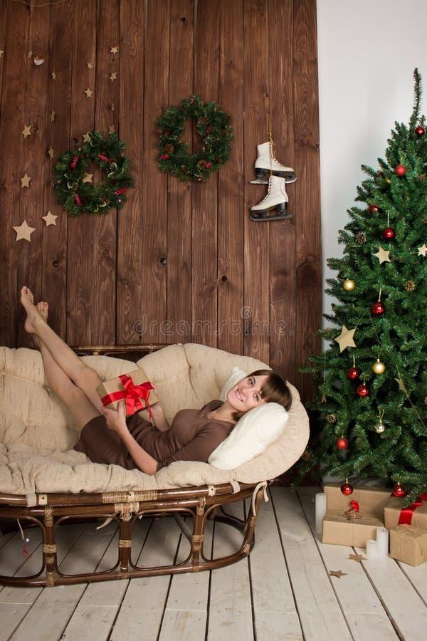 Junge Frau, die in der Hand auf der Couch mit einem Geschenk liegt lizenzfreie stockbilder