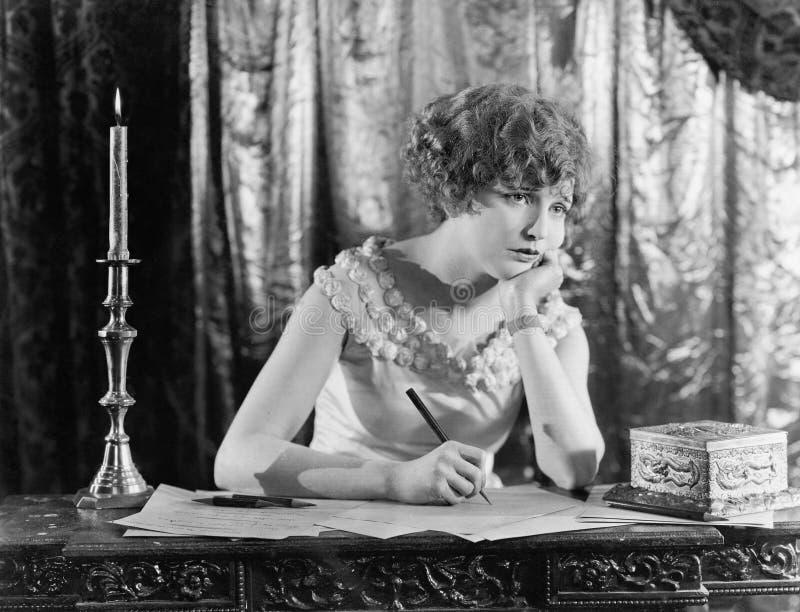 Junge Frau, die in der Hand an einem Schreibtisch mit einem Stift, schauend beim Schreiben eines Briefes sitzt traurig (alle darg lizenzfreie stockbilder